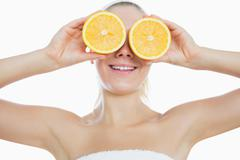 Woman holding slices of orange in front of eyes - stock photo