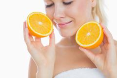 Woman with eyes closed holding slices of orange - stock photo