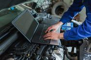 Stock Photo of Auto mechanic using laptop