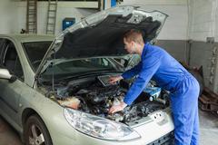 Mechanic examining car engine Stock Photos