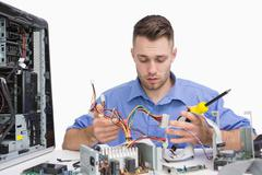 Young computer engineer working on cpu parts - stock photo