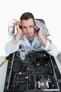 Portrait of tired young it professional with cables in hands - stock photo