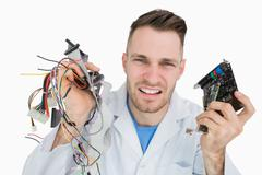 Portrait of young it professional yelling with cpu parts in hands - stock photo