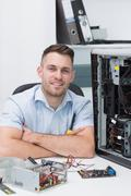 Smiling hardware professional sitting by an open cpu - stock photo