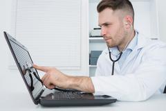 Hardware professional examining laptop with stethoscope Stock Photos