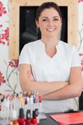 Stock Photo of Confident woman with arms crossed at reception in nail salon