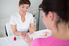 Nail technician applying nail varnish to finger nails Stock Photos