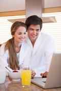 Stock Photo of Couple using laptop over breakfast