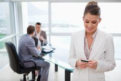 Colleagues in meeting with business woman text  messaging in foreground Stock Photos