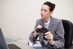 Business woman with binoculars looking at laptop - stock photo