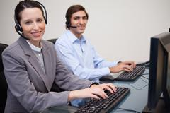 Happy call center employees at work - stock photo