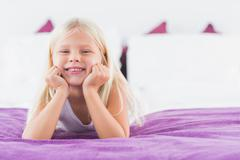 Little girl lying on a double bed Stock Photos