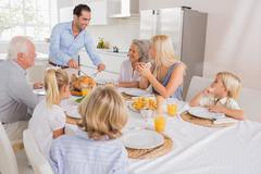Smiling father proposing a slice of turkey - stock photo