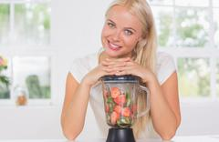 Smiling woman putting hands on the mixer - stock photo