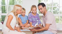 Calm family reading a story together - stock photo