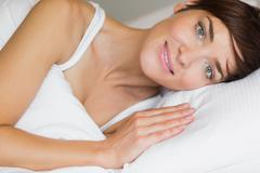 Stock Photo of Beautiful woman smiling in bed