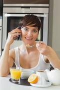 Stock Photo of Woman eating cereal and talking on phone