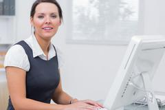 Stock Photo of Confident female executive using computer at office