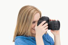 Side view of happy female photographer with photographic camera - stock photo
