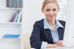 Stock Photo of Confident business woman with computer at office desk