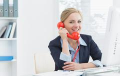 Smiling female executive using red land line phone at desk - stock photo