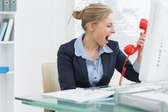 Female executive yelling into red telephone receiver at desk Stock Photos