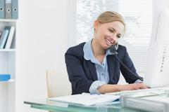Female executive using landline phone and computer at desk - stock photo