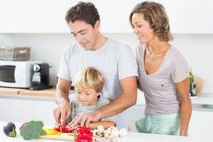 Stock Photo of Mother watching father teaching son to chop vegetables