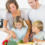 Stock Photo of Mother teaching daughter to slice vegetables as father and son are watching