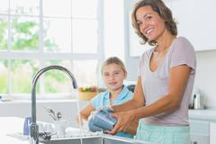 Happy mother and daughter doing the washing up - stock photo