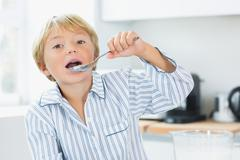 Cute boy eating cereal - stock photo