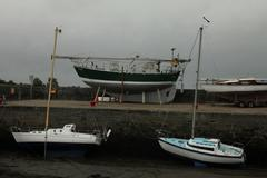 Boats in harbour at low tide. - stock photo