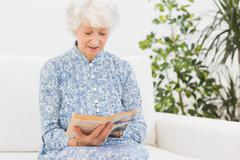 Elderly woman reading a old book Stock Photos
