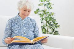 Elderly smiling woman looking at photos - stock photo