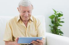 Elderly man using a digital tablet Stock Photos