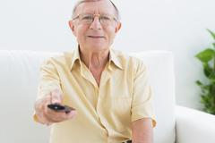 Smiling elderly man using the remote Stock Photos
