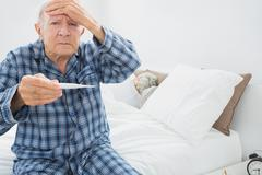 Old man with fever - stock photo