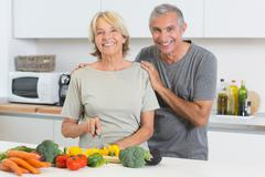 Stock Photo of Happy couple cutting vegetables together