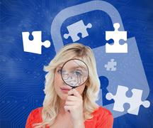 Stock Photo of Blonde looking through magnifying glass