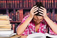 Stressed student in library - stock photo