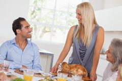 Stock Photo of Happy wife bringing turkey to the table