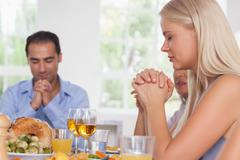 Woman saying grace with family before dinner - stock photo