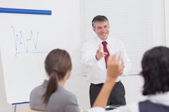 Stock Photo of Businessman pointing to colleague raising her hand with big smile
