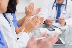 Nurses clapping a doctor - stock photo