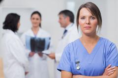 Nurse standing seriously with her team - stock photo