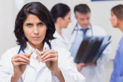 Doctor holding broken cigarette - stock photo