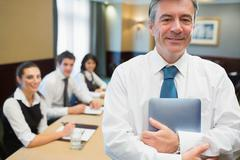 Businessman holding digital tablet at meeting Stock Photos