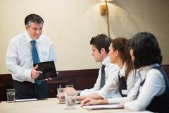 Businessman using tablet in meeting Stock Photos