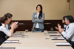 Stock Photo of Businesswoman being applauded by peers