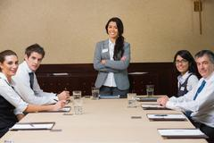 Smiling woman at head of business meeting Stock Photos
